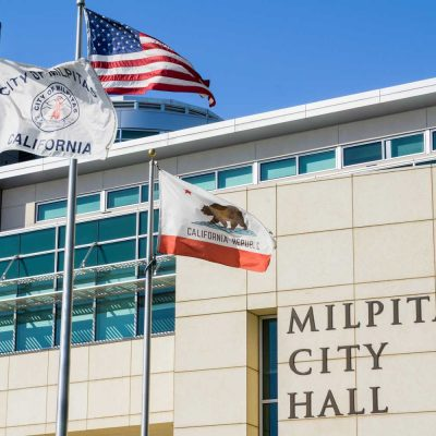 The City Hall Building on a sunny spring day; the City of Milpitas, USA and the State of California flags blowing in the wind — Photo by SundryPhotography